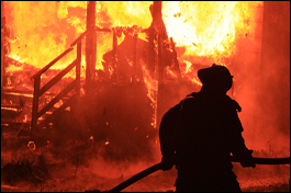 """alt=""""Burning house in flames with silhouette of fireman"""""""