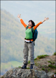"""alt=""""Woman hiker on top of mountain with her arms raised showing her happiness at her achievement"""""""