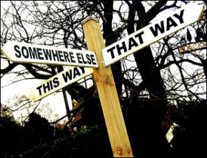 "alt=""Signpost at crossroad with signs pointing towards ""Somewhere else"" ""That way"" and ""This way"""""
