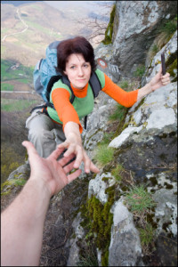 """alt=""""Woman hiker on a mountain reaching for another hiker's helpful hand"""""""