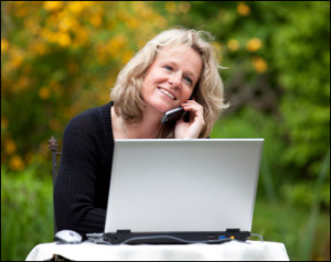 "alt=""Pleasant looking woman sitting with her laptop in a garden, talking on her cell phone"""
