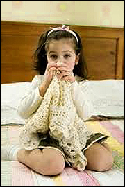 """alt=""""1950's Scared girl sitting on a bed, clutching a blanket"""""""