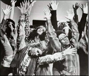 """alt=""""Dancers from the 1960's with long hair, beads, raising their hands"""""""
