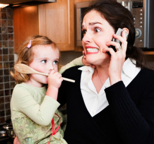 """alt=""""Stressed working mom holding a small child, talking on phone"""""""